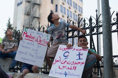 Children waiting to protest in the West Bank, under the security of an Israeli Watch Tower