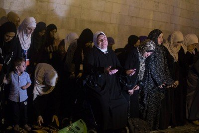 Women line up and pray on the streets outside Temple Mount, refusing to enter the compound.